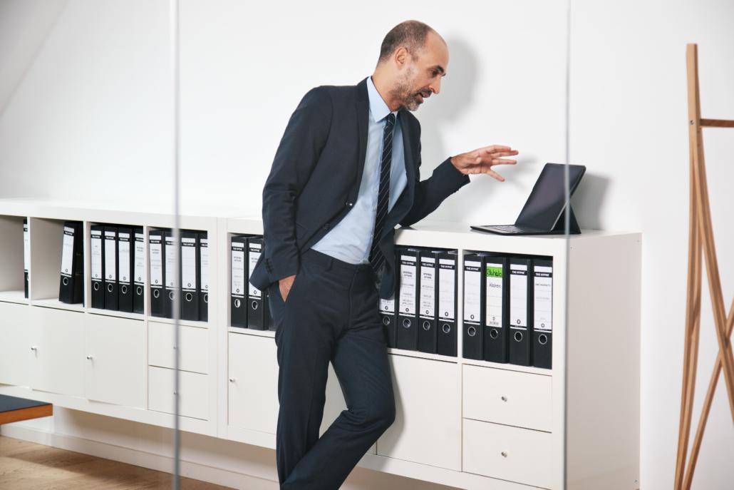 Mann im Anzug vor dem Laptop